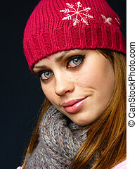 beautiful young girl in a red cap and a knitted scarf