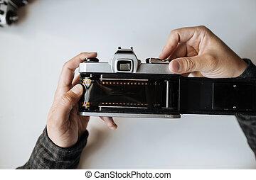 Vintage film camera. Men's hands recharge 35mm film