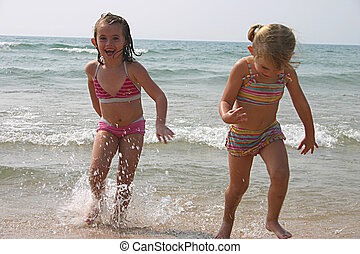 little girls playing at the beach