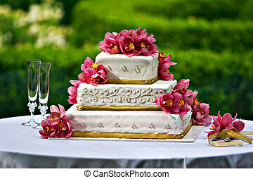 A three layered wedding cake with floral decortion