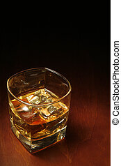 Whiskey in light pool on brown table with copyspace