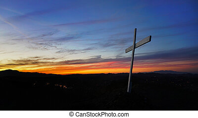 White cross on a hilltop at sunset