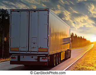 White truck on the rural road in evening