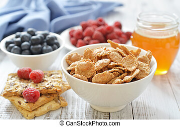 Whole-grain flakes in bowl with fresh berries on light background