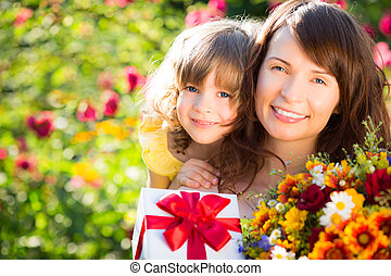 Woman and child with bouquet of flowers against green background. Spring family holiday concept. Mother`s day