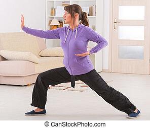 Beautiful woman doing qi gong tai chi exercise at home