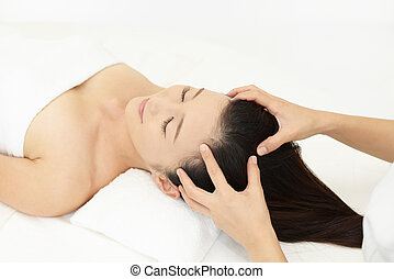 Woman in spa salon receives scalp massage
