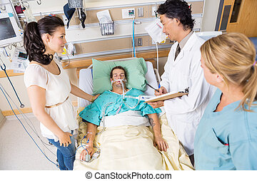 Woman Looking At Doctor Examining Patient