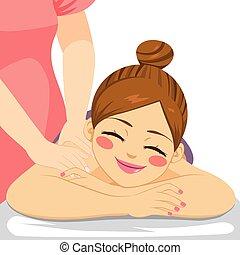 Woman enjoying relaxing wellness massage treatment lying down at spa