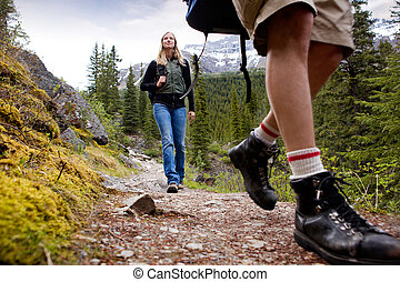 A happy woman on a mountain trail with mountains in the background
