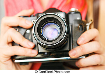 Woman photographer holding old 35mm film camera.