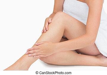 Woman sitting touching her legs wearing a towel
