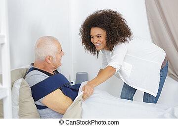 woman taking care of elderly man in nursing home