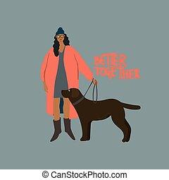 Woman with black Labrador dog on leash. Autumn walk