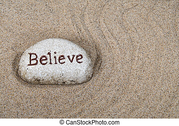 word believe on stone in sand