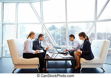 Photo of confident partners interacting at meeting in office