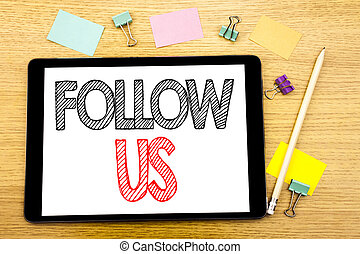 Writing text showing Follow Us. Business concept for Social Media Marketing Written on tablet laptop, wooden background with sticky note and pen