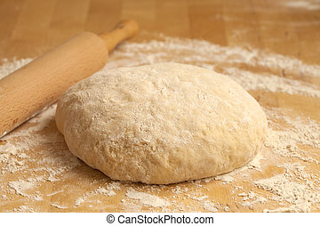 yeasty dough and rolling pin on wooden surface