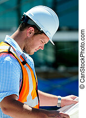 Young Attractive Male Civil Engineer, Checking The Blueprints