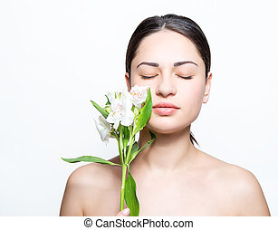 beautiful girl with a lily in the spa