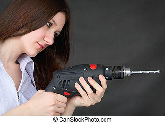 Young beautiful girl with drill in hands