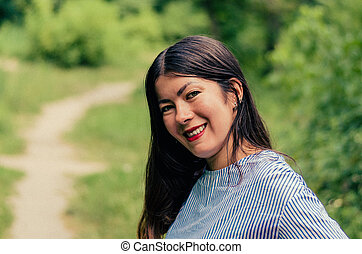 young beautiful smiling girl walks in a summer Park with green leaves