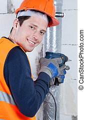 Young builder with drill in hands
