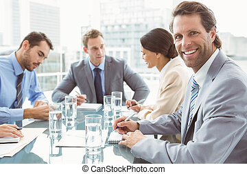 Portrait of young business people in board room meeting at office