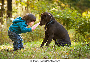 Young kid playing fetch game with dog and frisbee