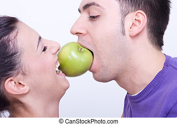 young couple with a green apple between their lips