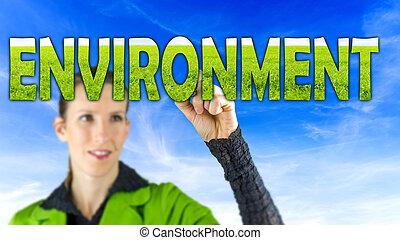 Young female environmental activist writing word Environment on virtual screen.