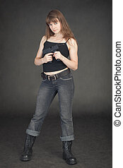 Young girl in jeans with an automatic pistol in hands