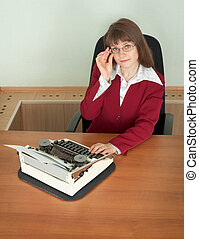 Young girl in office armchair with typewriter