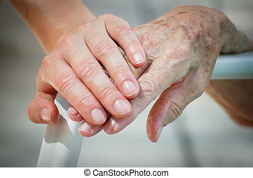 Young and old hand on a backrest