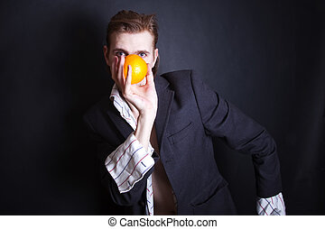 young man with an orange in his hand