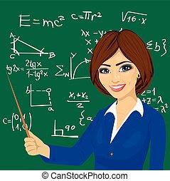 young math teacher standing next to blackboard