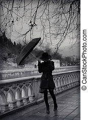 Young woman in coat with umbrella
