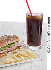 Yummy snack consisting of cola, ham sandwich and chips
